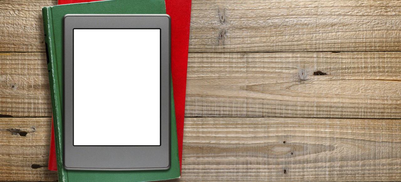 E-book reader and old books on wooden background